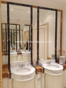 Miroir biseauté encastré dans une niche en marbre dans une salle de bain luxueuse